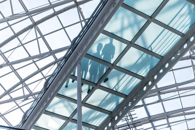 Low angle view of people walking on glass walkway