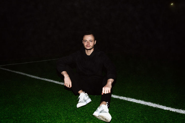 Portrait of young man on soccer field at night