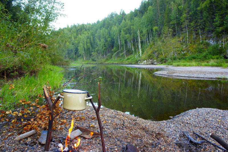 Saucepan Over Campfire At Riverbank In Forest