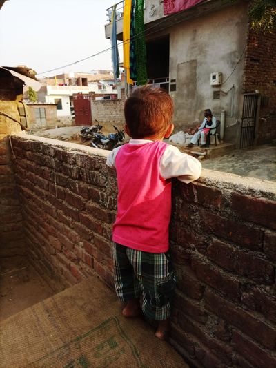 Rear view of boy standing against wall