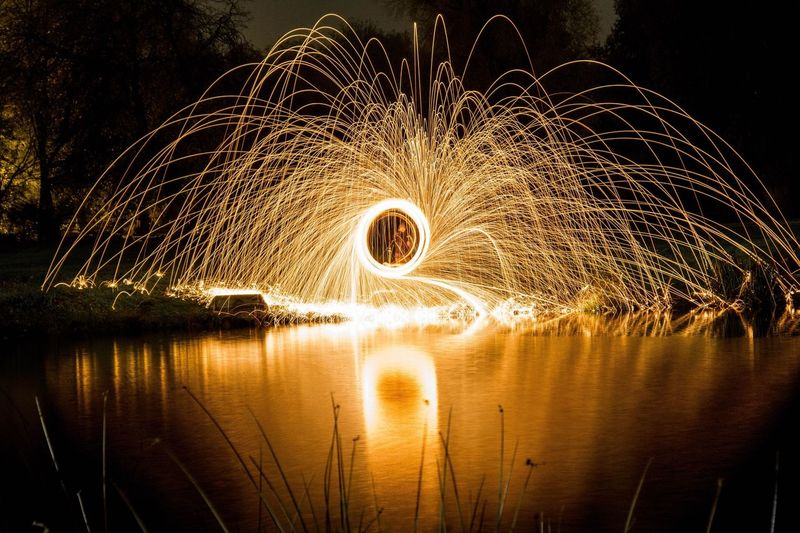 Person Spinning Wire Wool By Lake At Night