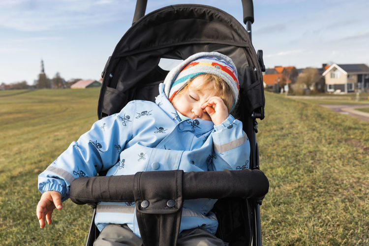 Child Sleeping On Stroller In Park