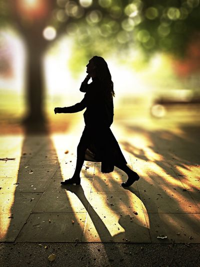 Tuning in. Silhouette Side View Lifestyles Full Length Street Road City Illuminated City Life Person Focus On Foreground Outdoors Backlit Loneliness One Woman Only Footpath