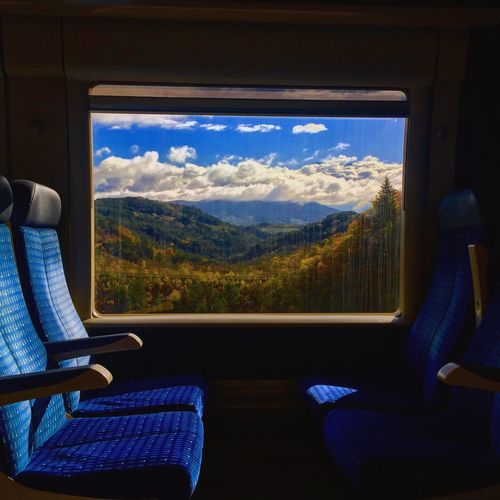 Vehicle Interior Window Glass - Material Transportation Sky Cloud - Sky Mode Of Transport Travel Landscape Journey Autumn Cloud Cloudy Travel Destinations Train Tree No People Blue Airplane Day Mountain Nature Vehicle Seat Scenics Mountain Range