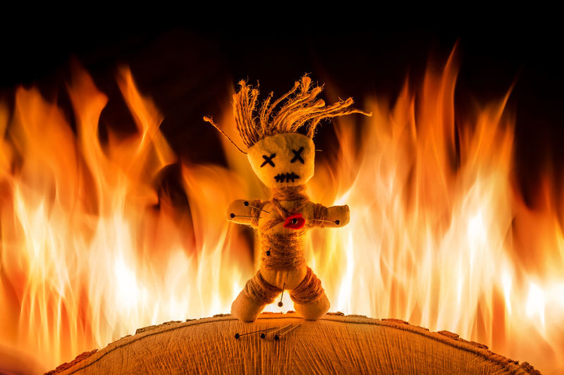 A needle punched voodoo doll stands in front of a bright fire