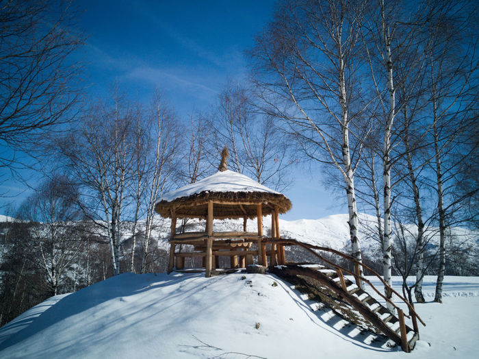 Built structure on snow covered land against sky