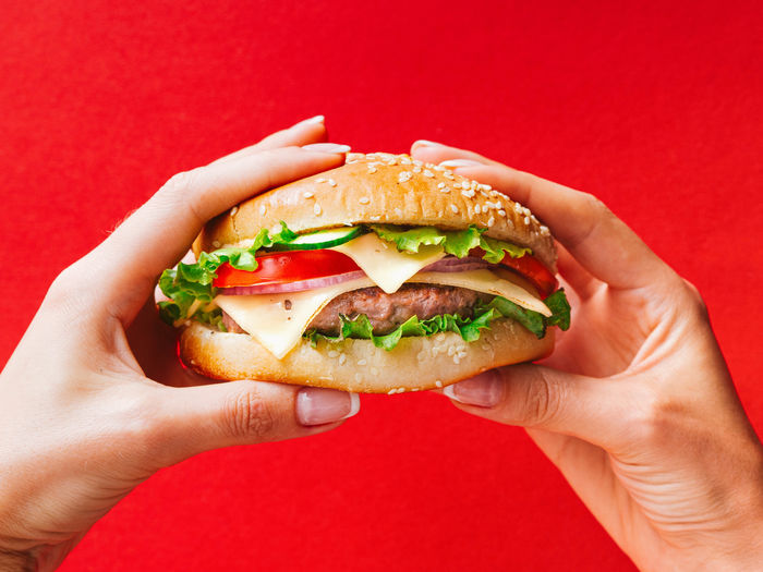 Close-up of hand holding burger against red background