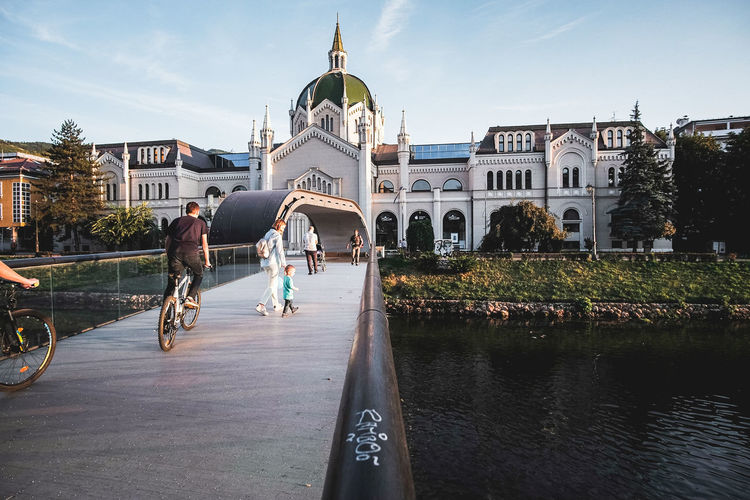 People riding bicycle by canal against buildings in city