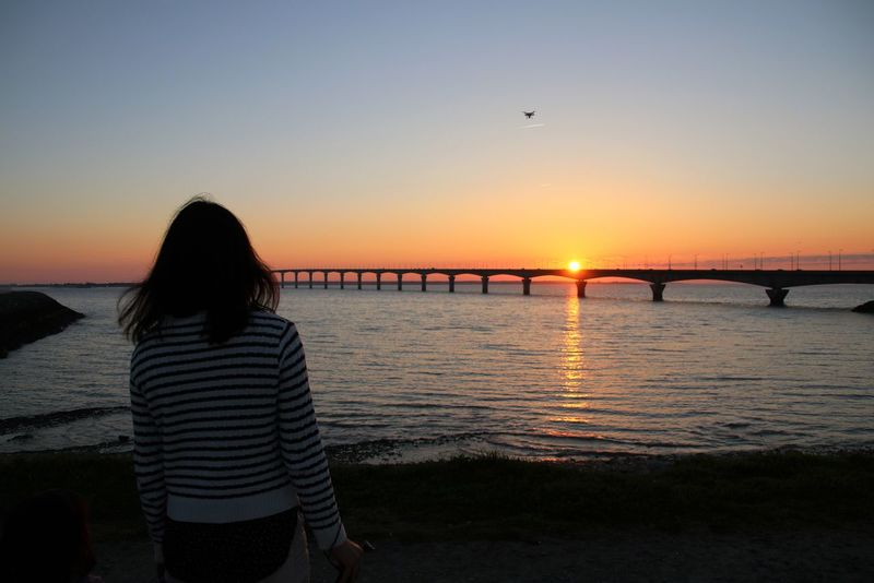Adult Adults Only Bridge - Man Made Structure Clear Sky Day Nature One Person One Woman Only Only Women Outdoors People Rear View Reflection Sea Silhouette Sky Sunset Travel Destinations Watching Water