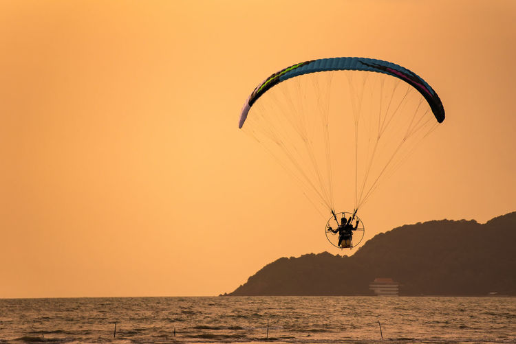 Silhouette Person Paragliding Above Sea Against During Sunset