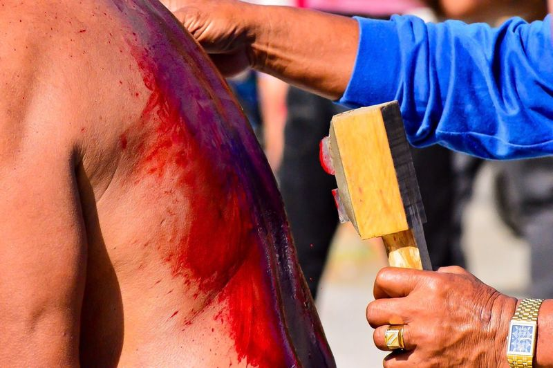 Cropped Hands Holding Blade By Injured Man During Festival