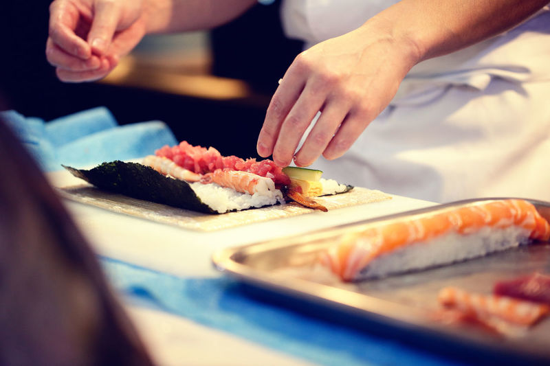 Midsection Of Chef Preparing Sushi In Restaurant