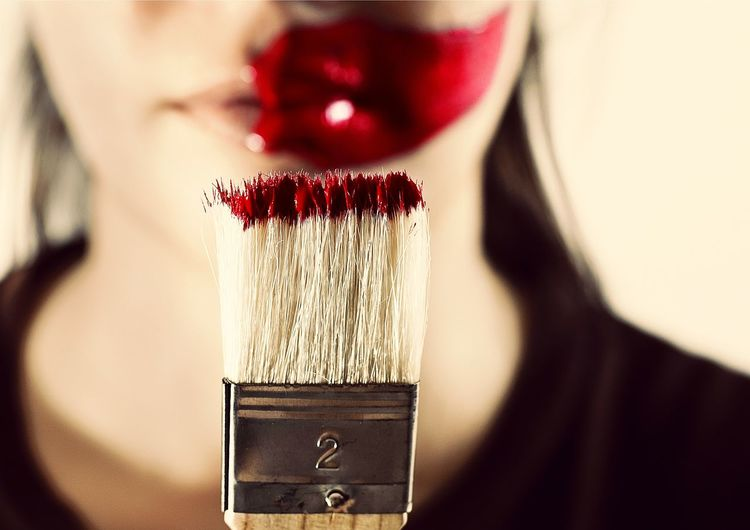 Close-up of woman with paintbrush against beige background
