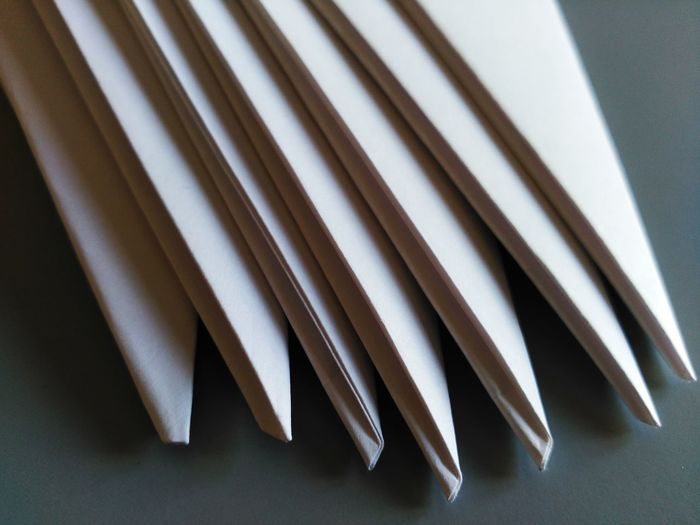 Close-up of folded white papers on table