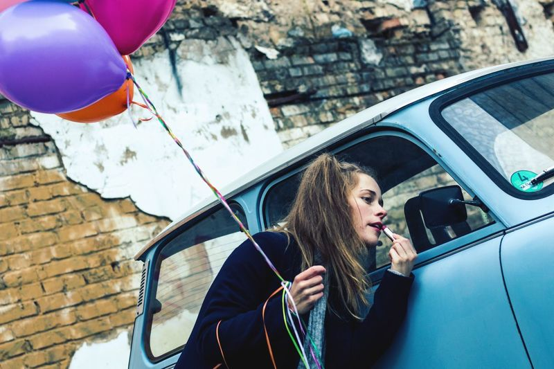 Young woman with colorful balloons applying lipstick while looking into side-view mirror of car