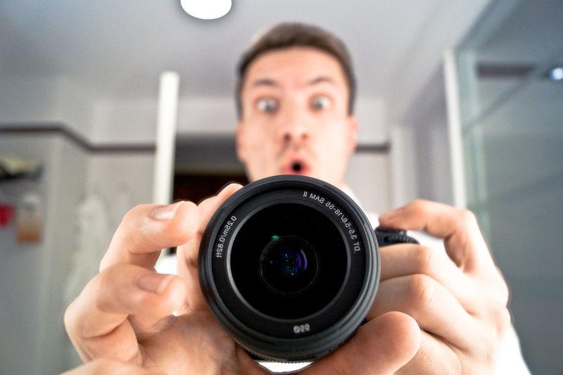 Shocked man holding camera