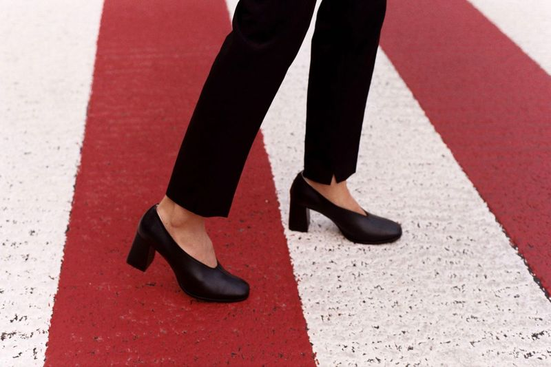 Low Section Of Woman Standing In High Heels On Zebra Crossing