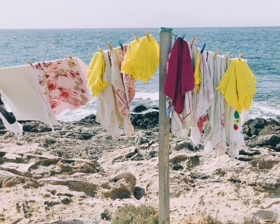 Sea Beach Horizon Over Water Water Nature Sand No People Outdoors Tranquility Drying Day Sky Beauty In Nature Multi Colored Washed Up Tranquil Scene Drying Clothes Freshness Colorful Sea And Sky Laundry Line Laundry Day Rock - Object Hanging Fresh