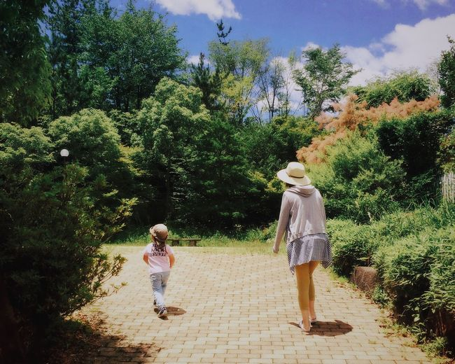 Rear view of mother and daughter walking in park