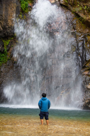 Rear view of man looking at waterfall in forest