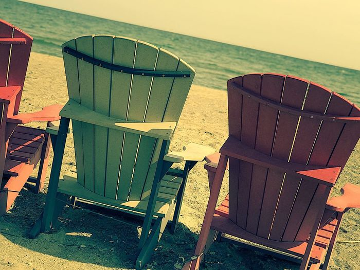 Empty chairs and tables on beach against sky