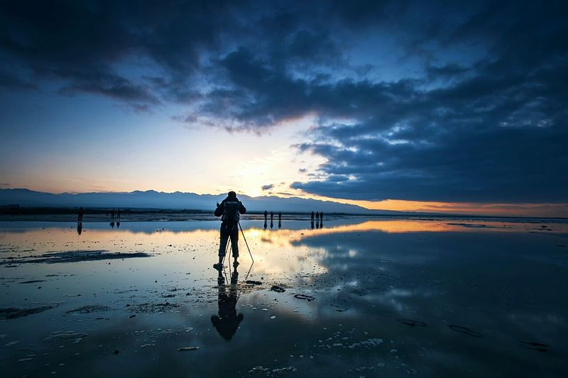 Rear view of photographer on wet shore against sky during sunset