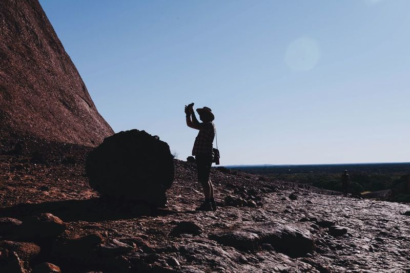 Man with arms raised standing at ayers rock in uluru-kata tjuta national park against sky