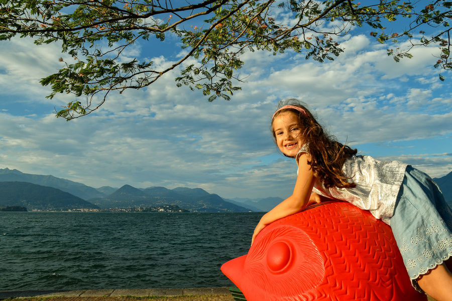 Little girl playing in a garden on the bank of the Maggiore Lake, Piedmont, Italy One Person Sky Lifestyles Water Smiling Cloud - Sky Real People Beauty In Nature Nature Leisure Activity Mountain Happiness Portrait Looking At Camera Plant Tree Outdoors Hairstyle Little Girl Lake Cracking Art Happy Playing Maggiore Lake Stresa Italy