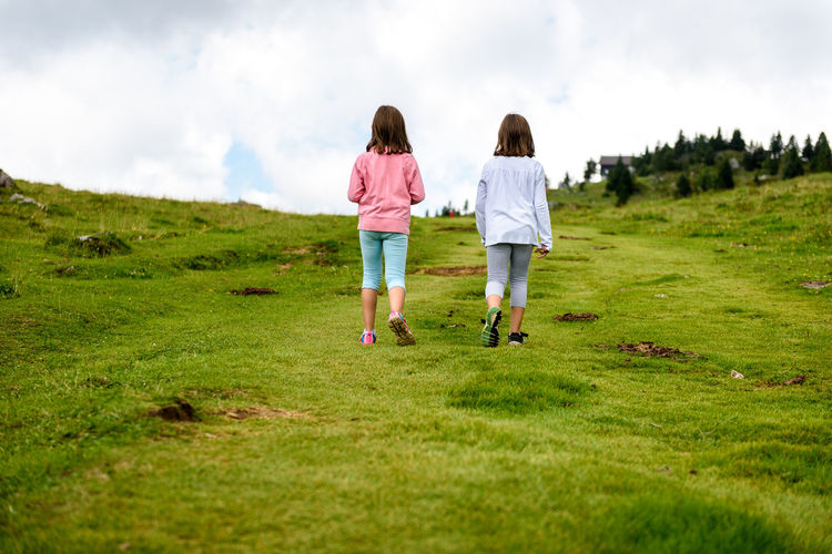 Rear view of women walking on field