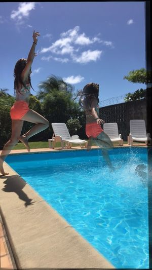 People jumping in swimming pool against sky