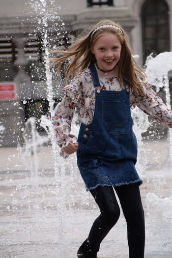 9 year old Emily Medcalf plays in water fountains in Queen Victoria Square, Hull Blond Hair Casual Clothing Cheerful Child Childhood Children Only Day Elementary Age Enjoyment Front View Fun Girls Happiness Lifestyles Long Hair Looking At Camera Motion One Girl Only One Person Outdoors People Portrait Smiling Standing Three Quarter Length