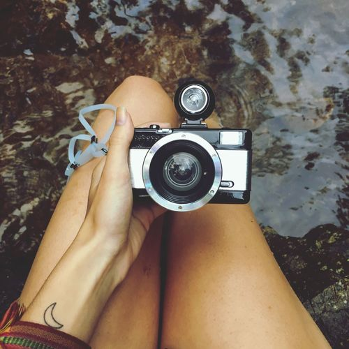 Midsection of woman holding vintage camera over water