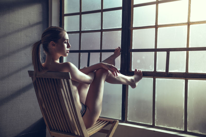 Topless woman sitting on char by window