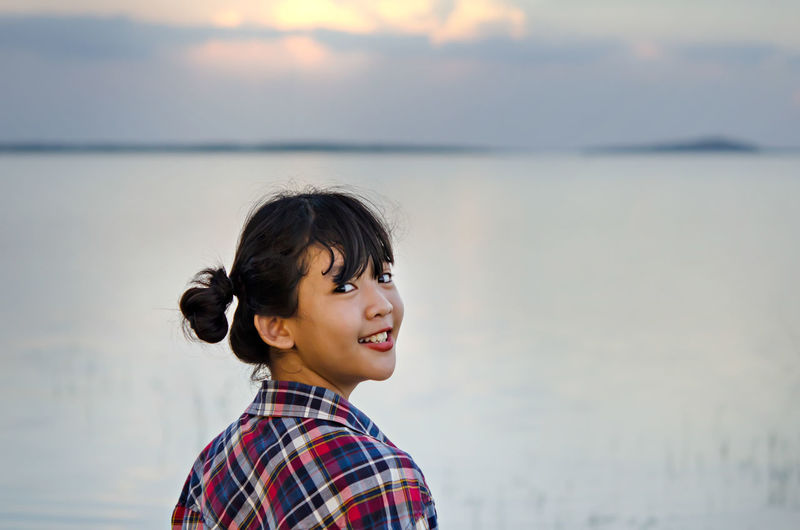 Portrait of smiling girl standing against sea