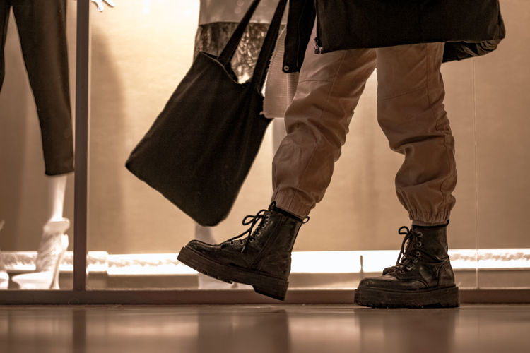 Low section of man walking on floor at shopping mall
