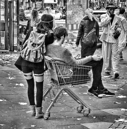Buy a man.... B&w B&W Collection B&w Photo B&w Photography B&w Street Photography Bnw_friday_eyeemchallenge Casual Clothing Chair Free Theme From My Point Of View Leisure Activity Lifestyles Malephotographerofthemonth Men Real People Shopping Side View Sitting Standing Street Street Photography Streetphoto_bw Togetherness Waiting Women