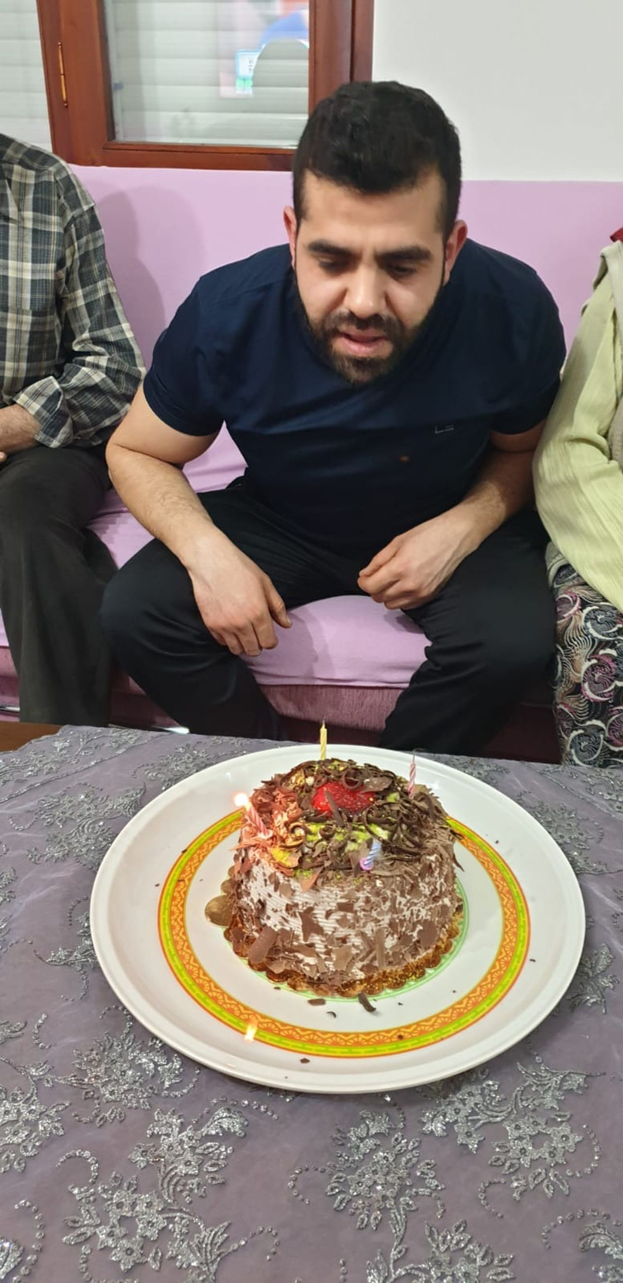 food and drink, food, real people, table, plate, indoors, front view, casual clothing, sitting, freshness, cake, lifestyles, people, sweet food, dessert, men, baked, sweet, birthday cake, temptation