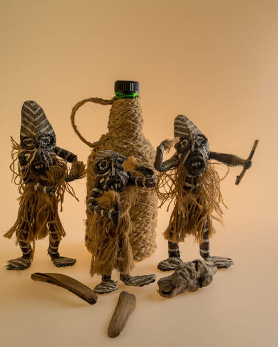 Three Afro-Brazilian Priests dancing to praise God Cachaça AFRICAN CULTURE Art And Craft Creativity Bottle Cachaça Close-up Day Dolls Indoors  No People Still Life Studio Photography Studio Shot Sunset Table White Background Wood - Material