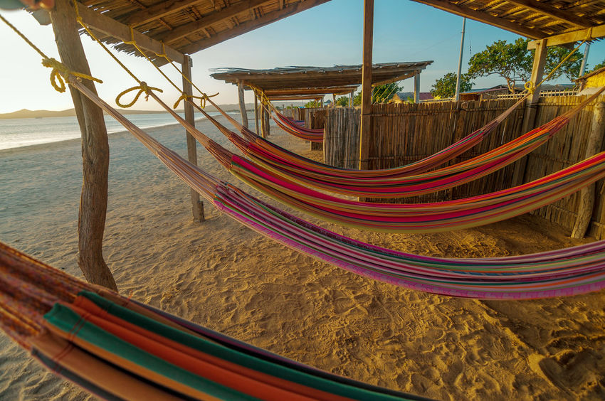 Colorful hammocks on a beautiful deserted bach in Cabo de La Vela in La Guajira, Colombia America Arid Beach Colombia Countryside Desolate Dry Environment Guajira Holiday Hot Isolated Ocean Outdoors Paradise Relaxation Sand Sea Shore Silhouette South Sun Sunset Tropical Vacation