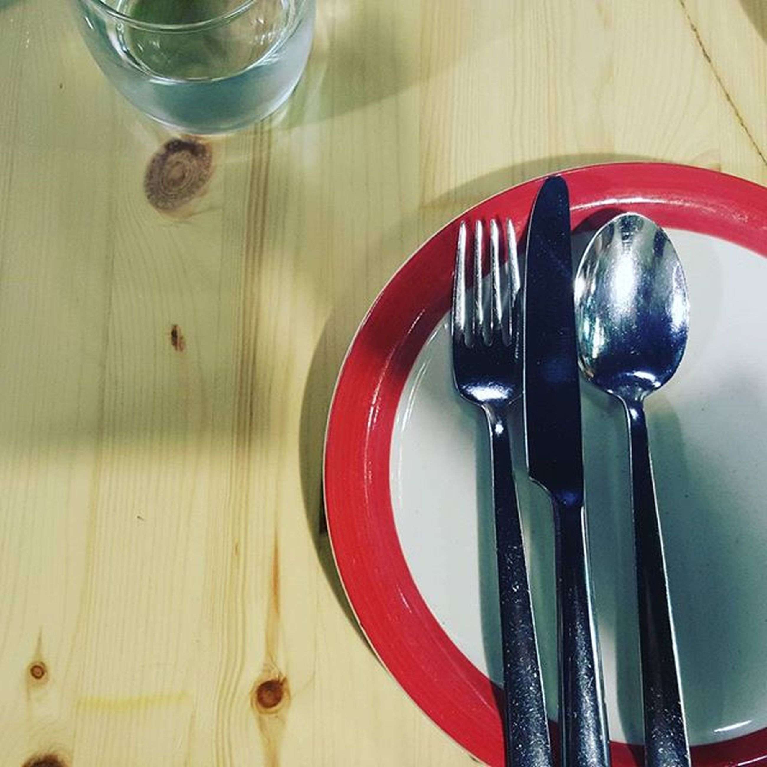 indoors, table, still life, food and drink, fork, spoon, high angle view, close-up, drinking glass, drink, food, plate, freshness, wood - material, directly above, red, no people, table knife, refreshment, glass - material