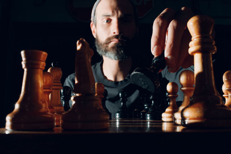 Full length of man relaxing on chess board