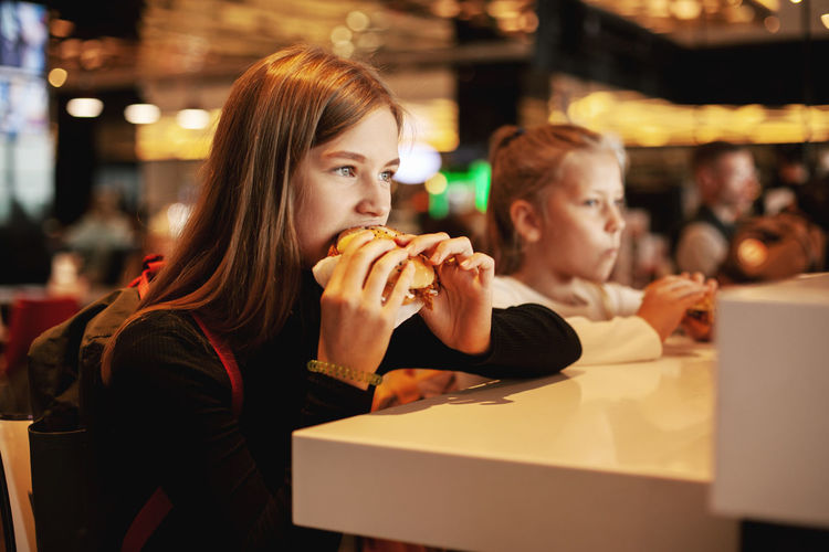 Beautiful schoolgirl eating hamburger sitting in a cafe