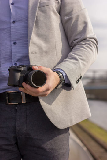 Midsection of man holding camera