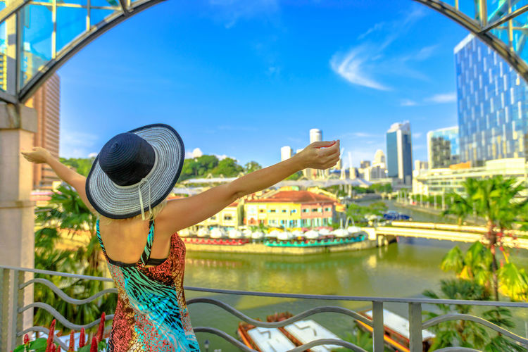 Tourist woman with wide hat looking panorama from terrace over Clarke Quay and Riverside area in Singapore, Southeast Asia.Cruise on Singapore River in sunny day and skyscrapers downtown on background Singapore Singapore City Woman Tourist Tourist Attraction  Tourist Destination People Girl Females Aerial View Skyline Cityscape Panorama Happy Travel Hat Lifestyle Enjoy Nature Tourism River Clarke Quay Clarke Quay, Singapore Boats Cruise Architecture Built Structure One Person Water Real People Clothing Building Exterior City Day Focus On Foreground Leisure Activity Lifestyles Women Adult Sky Transportation Outdoors