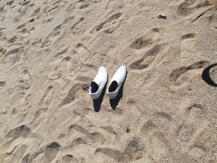 Close-up of footwear on sand