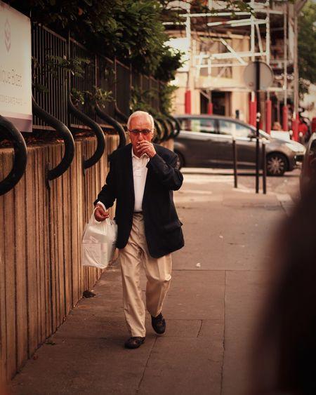 Senior Man Smoking Cigarette While Walking On Sidewalk In City