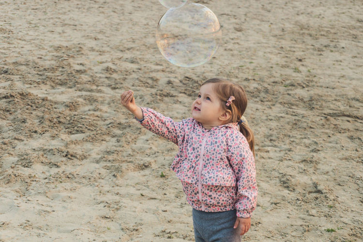 Cute girl playing with bubbles on beach