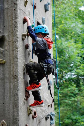 Full length of boy climbing on rope