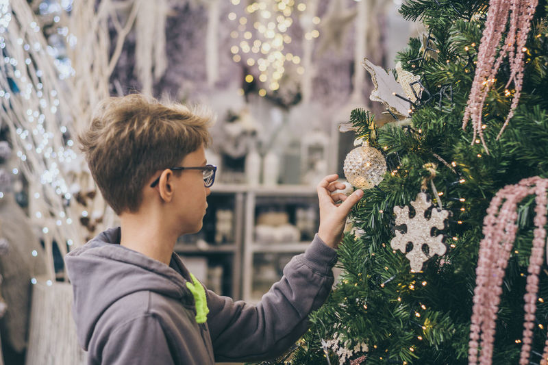Portrait of man holding christmas tree during winter