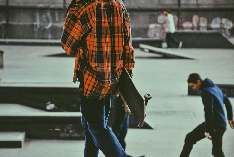 Man walking with skateboard in skateboard park with friends skating in background